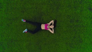 sports woman resting after workout lying on grass. top view. frame from height