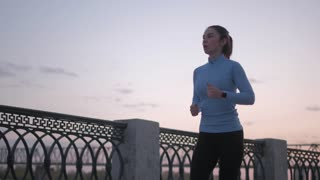 sporty girl in a smart watch jogs along the embankment at sunset. portrait of a sportswoman taking a sport in nature