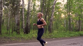 strong girl Jogging in a summer forest. muscular athlete is running in the nature. slow motion