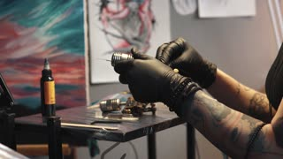 tattoo artist collects the tattoo machine. girl tattoo master prepares a rotary tattoo machine gun for drawing a drawing on the skin