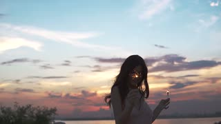 The girl happily dances at sunset. Young woman in a cocktail dress having fun holding bengal lights. slow motion