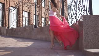 the girl in the red dress walking down the street in the setting sun. slow motion