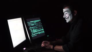 The hacker in the mask hacks the program. the digital extortion gets access to other people's information. computer virus attack