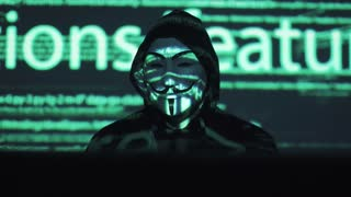 theft of personal data on the network. robber in the mask and hood against the background of the running code. anonym uses a computer to break into the system