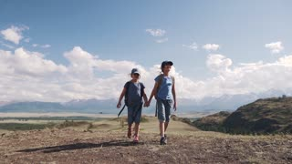tourism with children. children travelers. two little girls with backpacks go on a hike and hold hands.