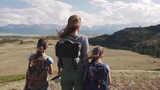 tourists in the mountains. a young mother and her daughters teenagers in a hike. woman with children admiring the stunning views of the mountains