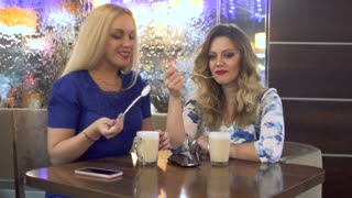 Two attractive girls have fun chatting in a cafe