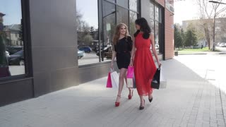 two best friends go shopping. Blonde and brunette walking down the street with shopping bags. Attractive girls are walking around the city. SLOW MOTION