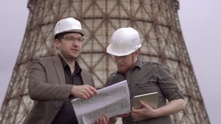 two businessmen in the construction helmets on the background of the nuclear power plant. architects holding a building plan and talk