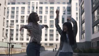 two crazy girls dancing and fooling around outdoors. slow motion