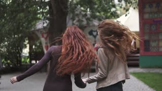 two crazy redheads girlfriends having fun, frolic and jump. the view from the back. slow motion