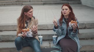two girlfriends eating hamburgers outdoors. 20s