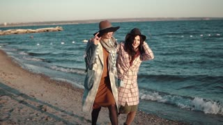 two girlfriends happily run around and frolic in the open air. young woman in autumn coat and hat on the beach at sunset. Slow motion