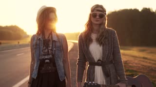 Two hippie girls walk along the freeway at dawn