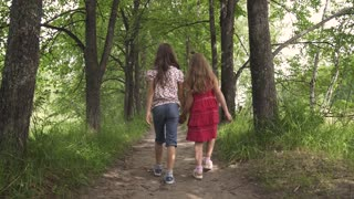 two little girls hold hands and walk down the green alley. children walk outdoors. two little sisters