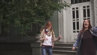 Two red-haired girls are crazy dancing on the street. slow motion