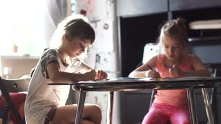 two sisters 6 and 7 years drawing together sitting at the table. children draw with crayons in the sun