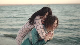 two young attractive girls have fun and embrace. best friends spend time together outdoors by the water. portrait of girlfriends on the beach at sunset
