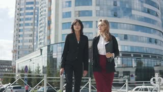 two young attractive women in formal suits go against the background of a modern business center