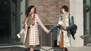 two young beautiful girls walking through the spring city and holding hands
