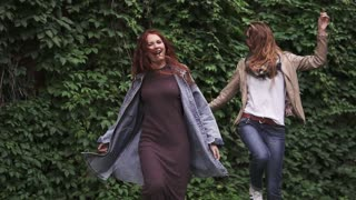 unbridled joy of two redheaded girlfriends. girls fooling around, having fun, laughing and jumping. girlfriends having fun together. slow motion