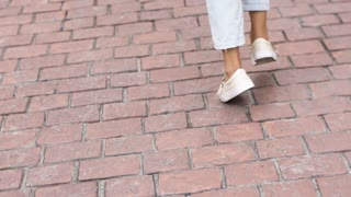 woman feet closeup. girl in sneakers is on the pavement. Female feet dancing. Close-up shot of dancing legs walk and dancing. slow motion