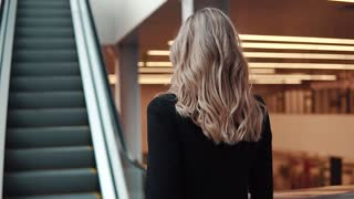 woman in a business suit rises on an escalator in a large business center. business woman holding documents. back view