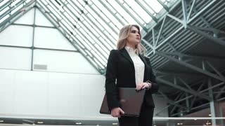 woman in a business suit with a laptop in hands on a modern business building background. business woman expects a client or business partner