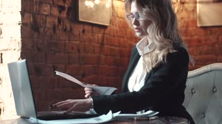 woman in business suit reprinting document on laptop