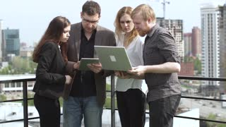 Working meeting in an informal setting on the roof of the business center. A group of young businesspeople talking and working on a laptop