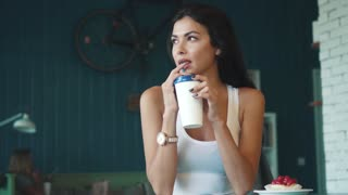 young attractive woman drinking coffee from a paper Cup at the coffee shop