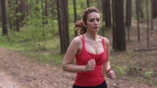 young attractive woman Jogging in a summer forest. girl with wireless headphones and a watch with heart rate monitor sports. sprotsmen training. slow motion