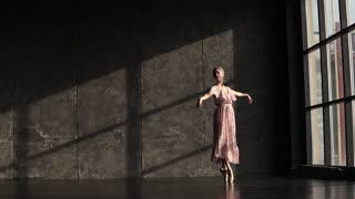 young beautiful ballerina in a long fluttering dress dancing classical ballet. Ballet dancer in pointe shoes. slow motion