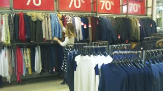 young beautiful girl chooses clothes in shop. woman shopping