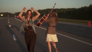young beautiful girl in the hippie clothes walking on a deserted road at dawn and fun dancing. Slow motion