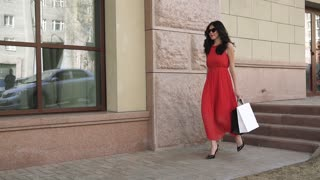 young beautiful girl is walking down the city street with shopping bags after a successful shopping. Brunette in a dress, sunglasses and high-heeled shoes. Slow motion