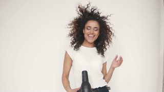 young curly-haired girl sings in a hair dryer and dances at home