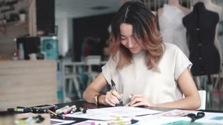 young fashion designer girl makes a sketch in pencil at the atelier. business woman with Asian appearance working in the office