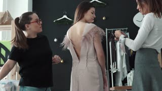 Young fashion designer, tailor and dressmaker adjusting clothes per customer. creator of clothes and the assistant work in the atelier