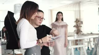 Young fashion designer, tailor and dressmaker works with an assistant and looks at the sketch of clothes