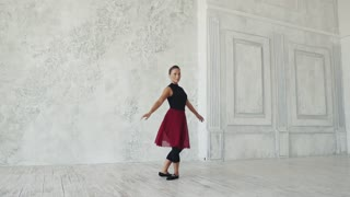 young female dancer dancing on a light background. slow motion