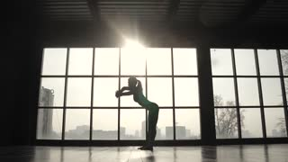 young flexible girl doing warm-up before training on the background of a large window. girl practicing yoga