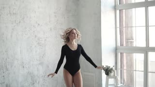 young girl dancer in black bodysuit and leggings. ballerina is dancing and makes a pirouette. slow motion