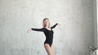 young girl dancer in black bodysuit and leggings. ballerina is dancing. slow motion
