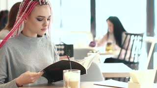 young girl hipsters leafing through the menu in the cafe