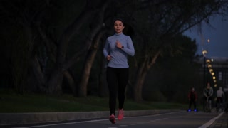 young girl in sports clothes Jogging in the Park late at night. outdoor sports. slow motion