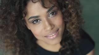 young hispanic woman with curly hair and brown eyes smiling at the camera