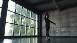 young male ballet dancer dancing in studio on a dark background. slow motion
