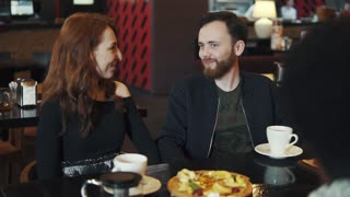 young man and a girl sitting at a table in a cafe or restaurant and talking fun