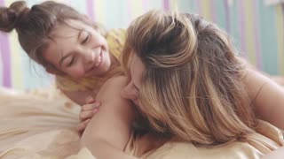 young mom and her little daughter hugging and laughing